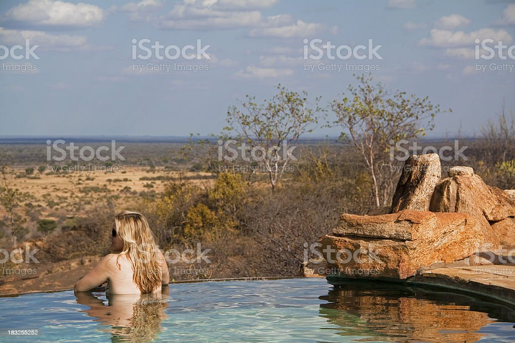 Girl in safari lodge pool stock photo