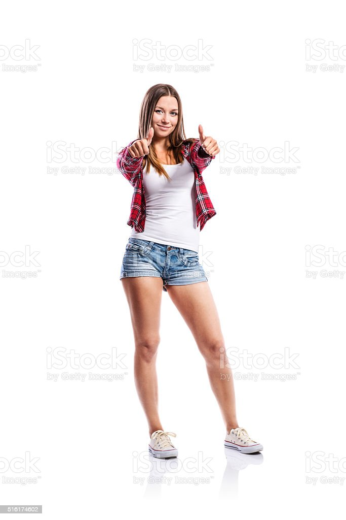 Girl in shorts and checked shirt, thumbs up, isolated stock photo
