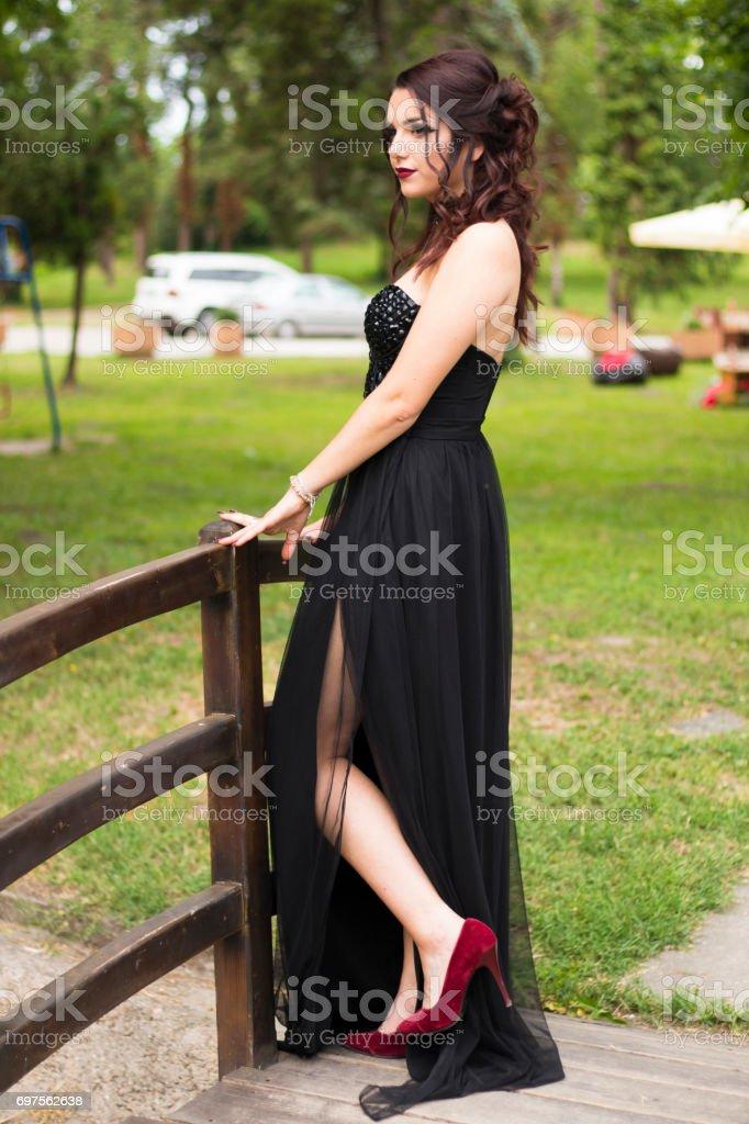 Girl in slit dress standing on small bridge in park stock photo