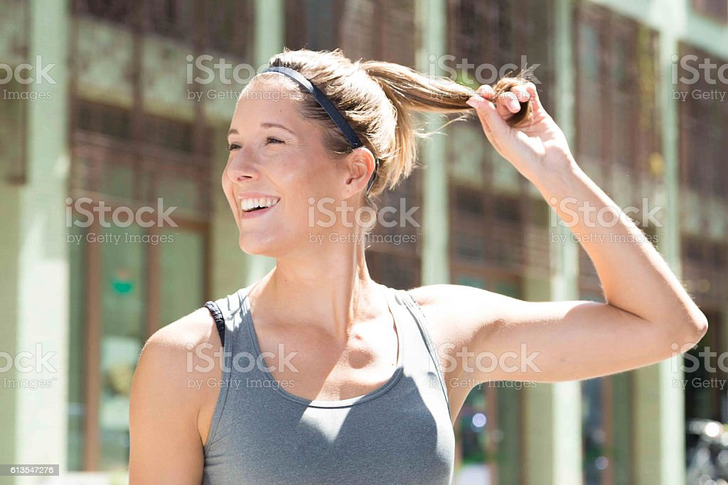 Girl in sports-clothing posing standing on the street stock photo