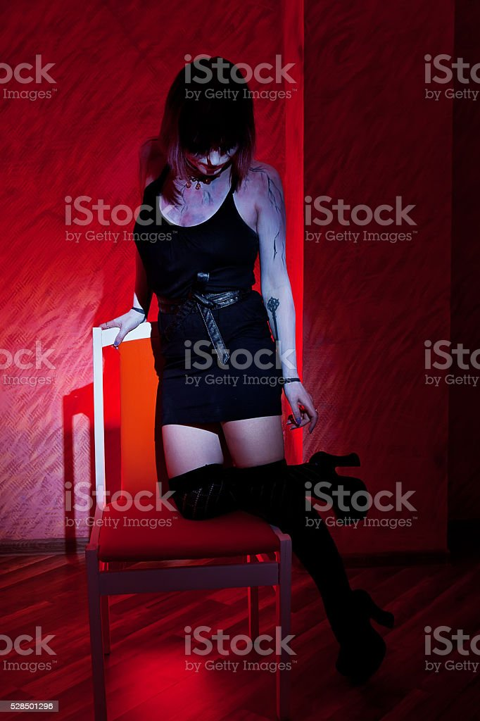 girl in stockings posing in chair against a red stock photo