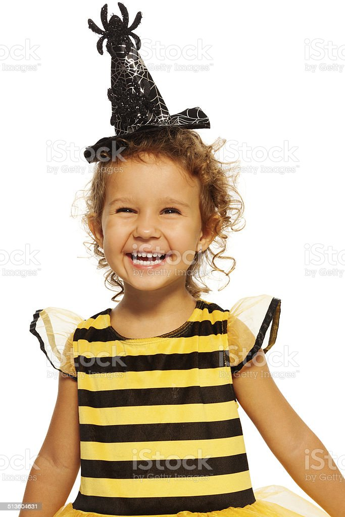 Girl in striped bee costume wearing spider hat stock photo