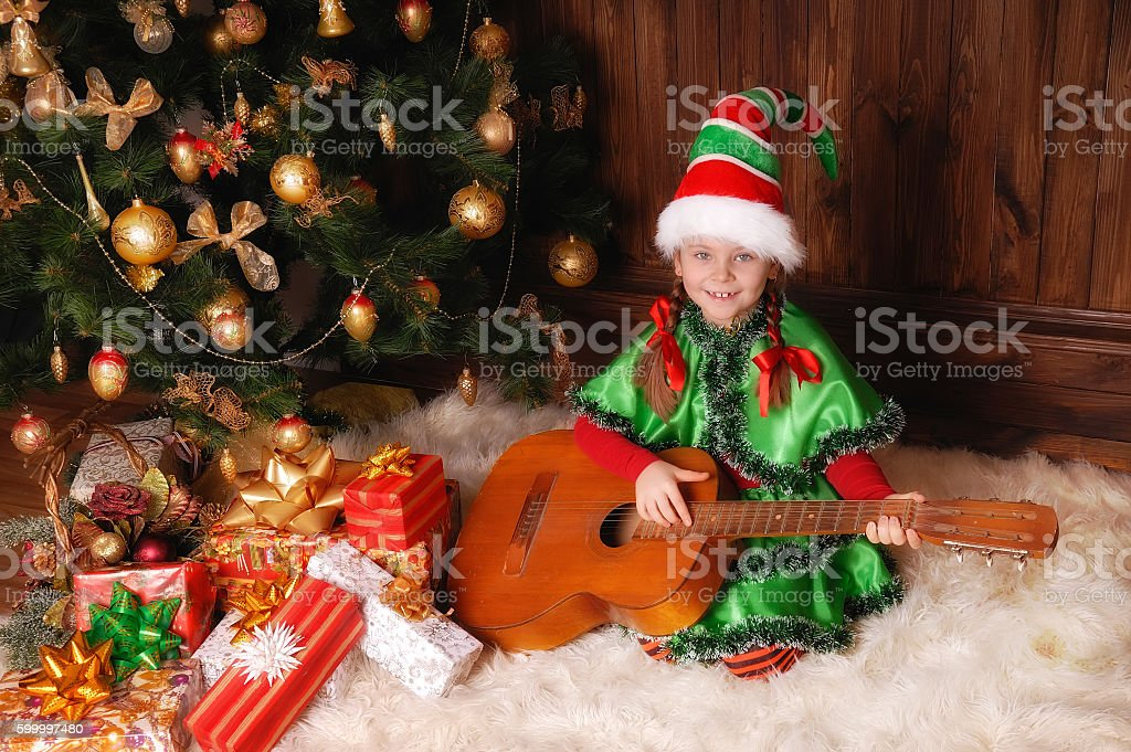 Girl in suit of the Christmas Elf with a Guitar stock photo