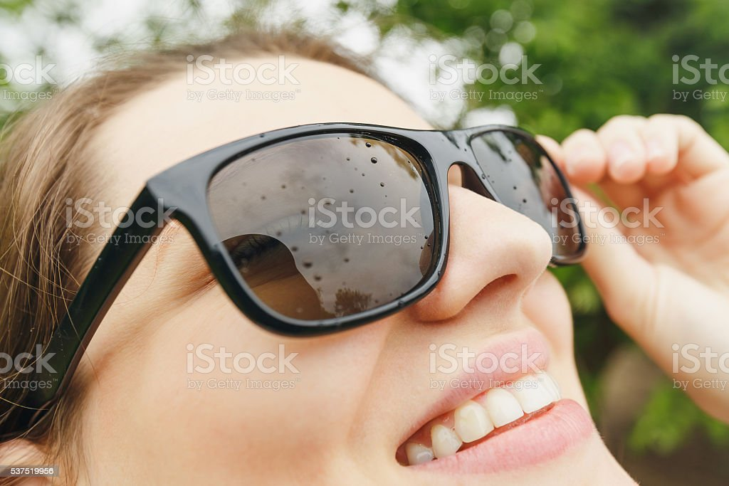 girl in sunglasses rain looking at the sky stock photo