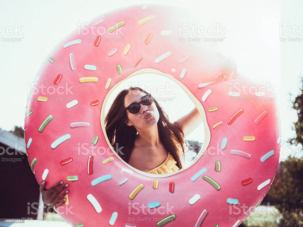Girl in sunglasses with a pool inflatable blowing a kiss stock photo