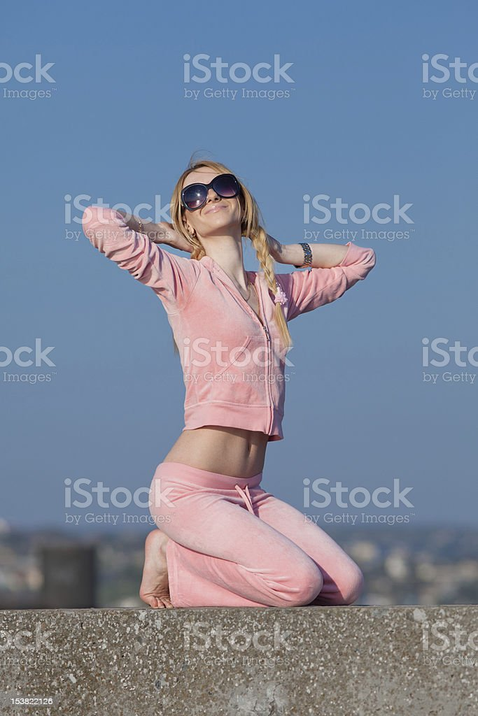 Girl in sunglasses with arm raised on background of sky royalty-free stock photo