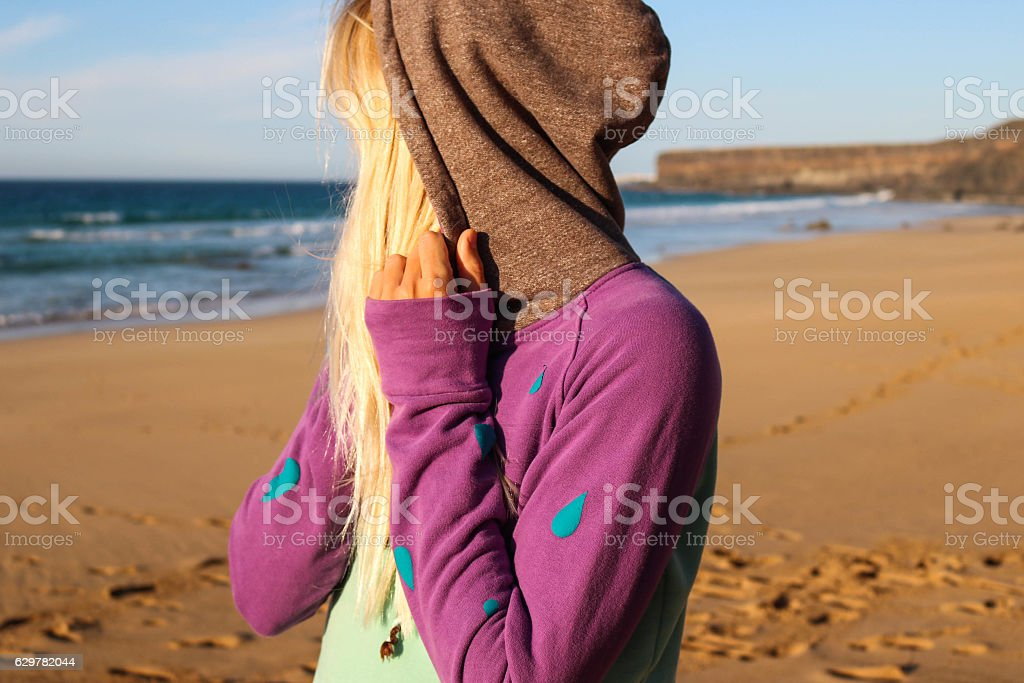 Girl in sweather on the beach stock photo