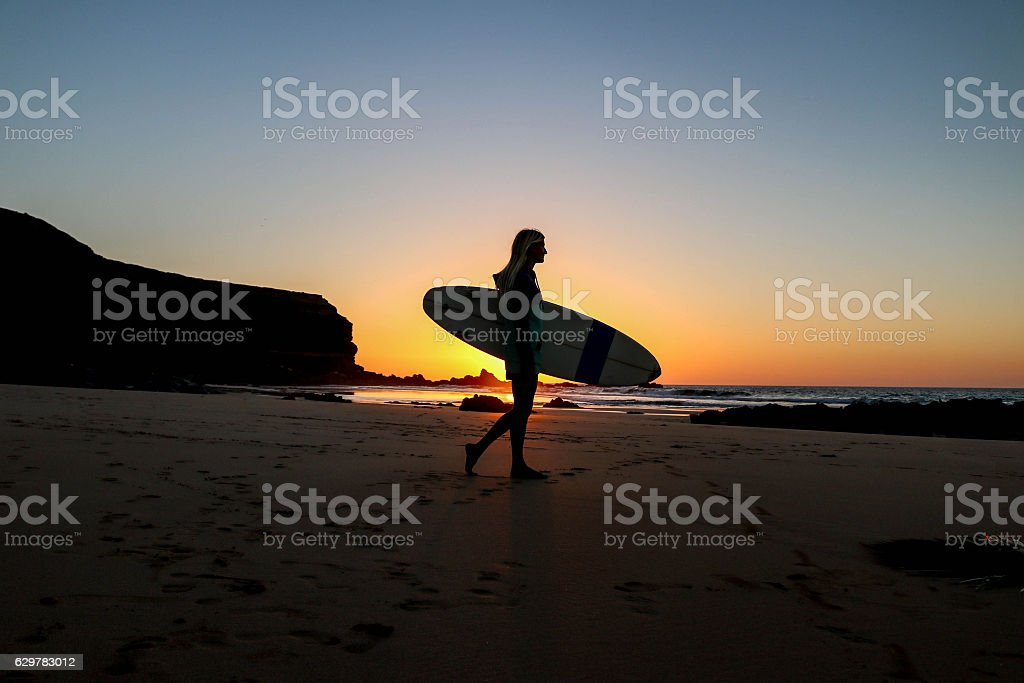 Girl in sweather with surfboard on the beach in sunset stock photo