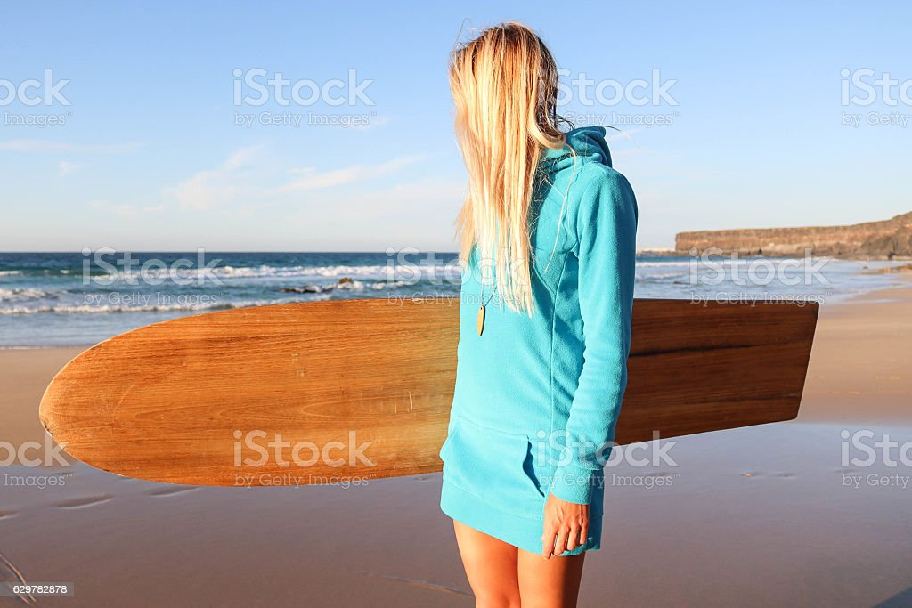 Girl in sweather with surfboard on the beach stock photo