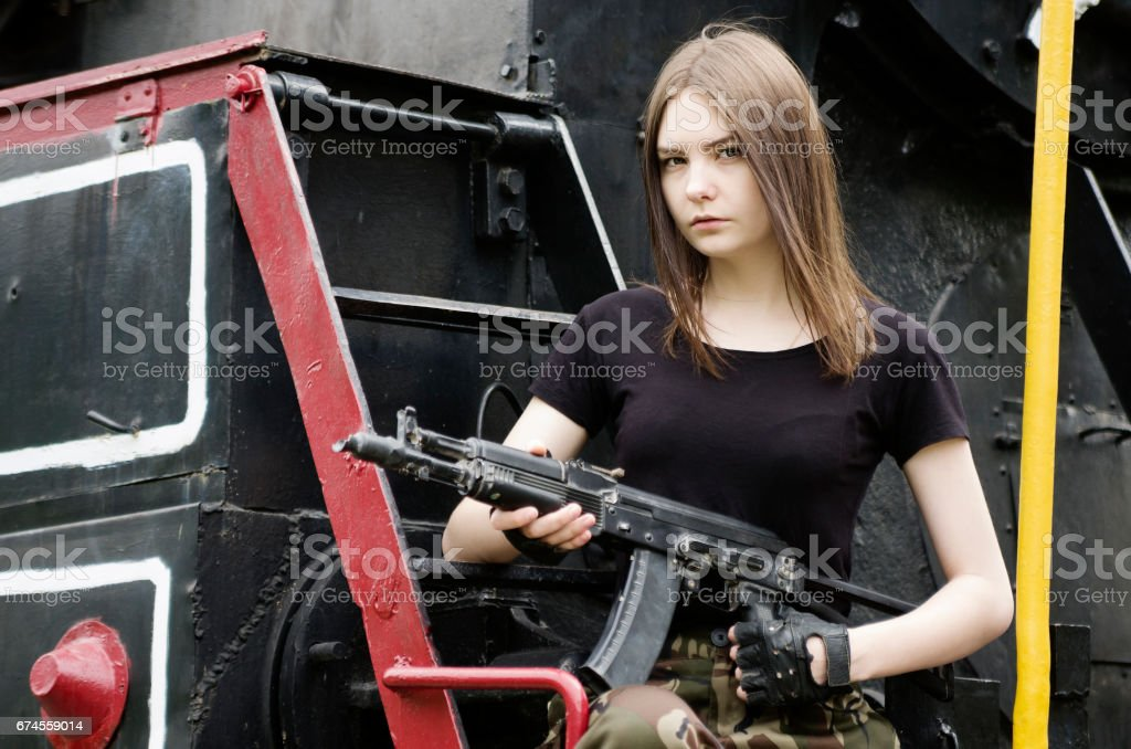 Girl in the black T-shirt with a gun, posing near a locomotive stock photo