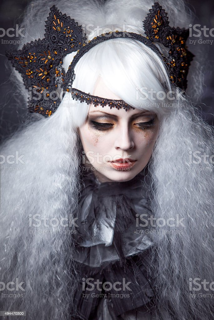 girl in the image of  witch with a lush white stock photo