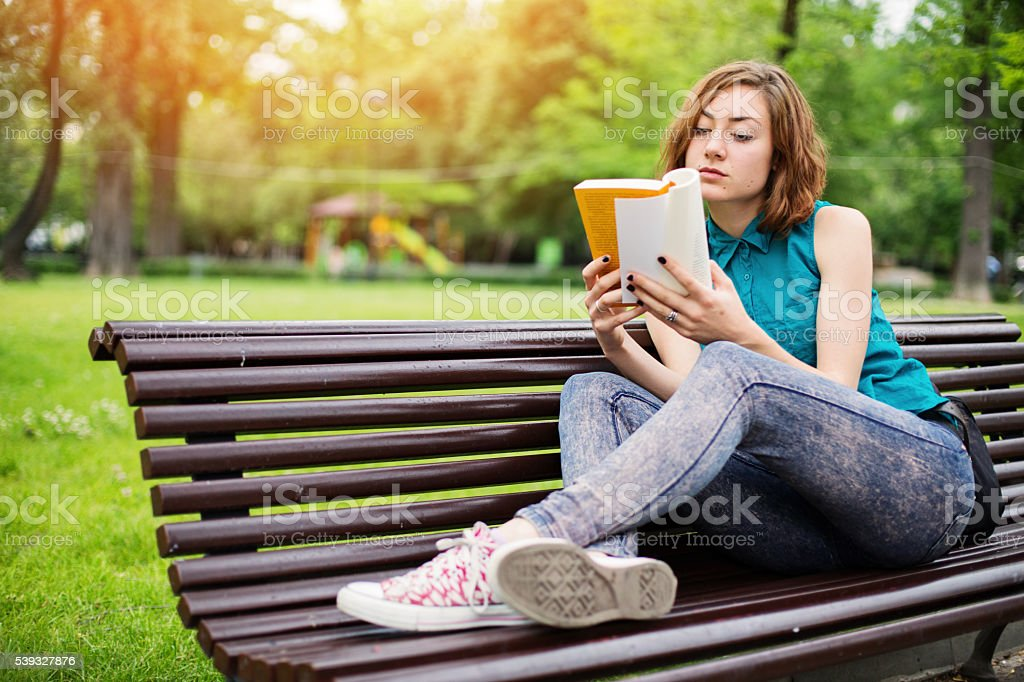 Girl in the park reading a book stock photo