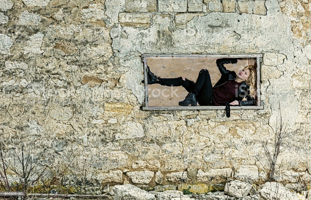 Girl in the window frame of ruined building stock photo