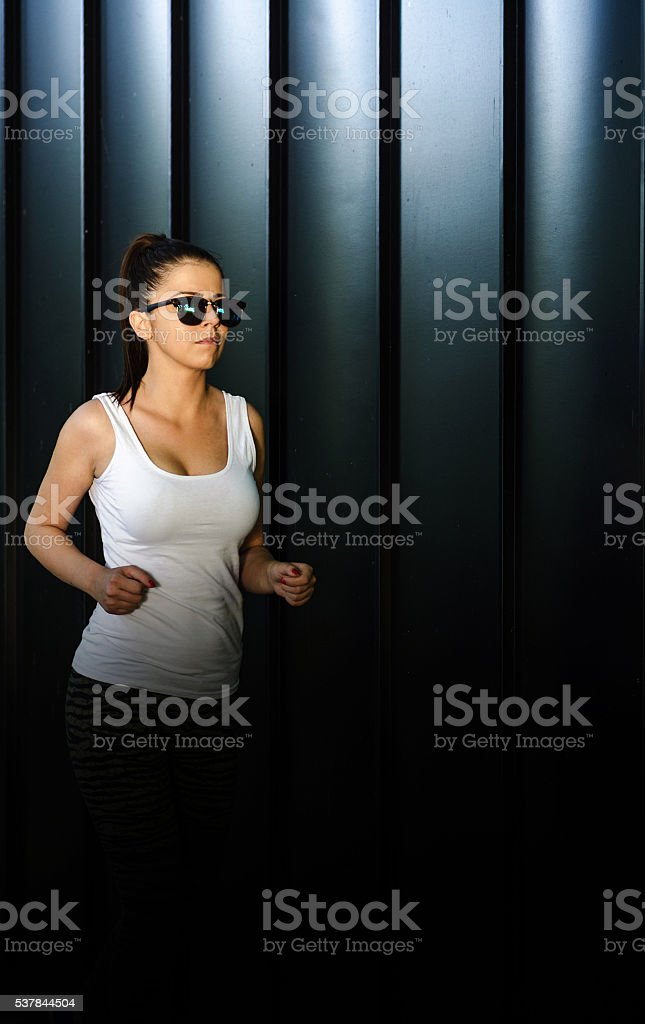 girl in tights running against a wall or metal billboards stock photo