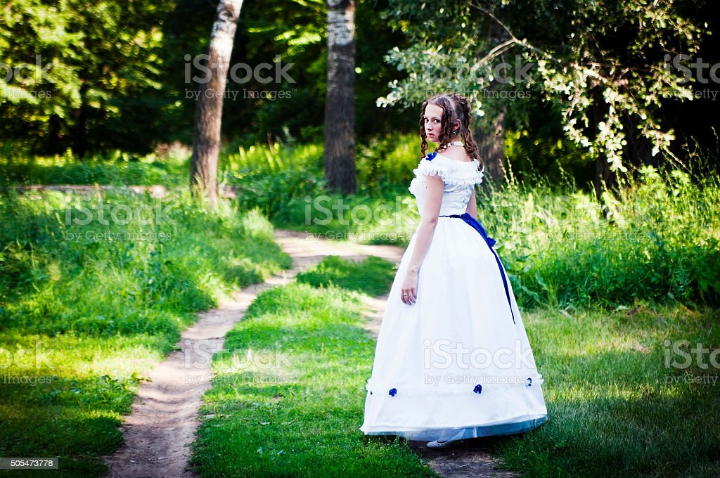 Girl in vintage dress goes along forest road stock photo