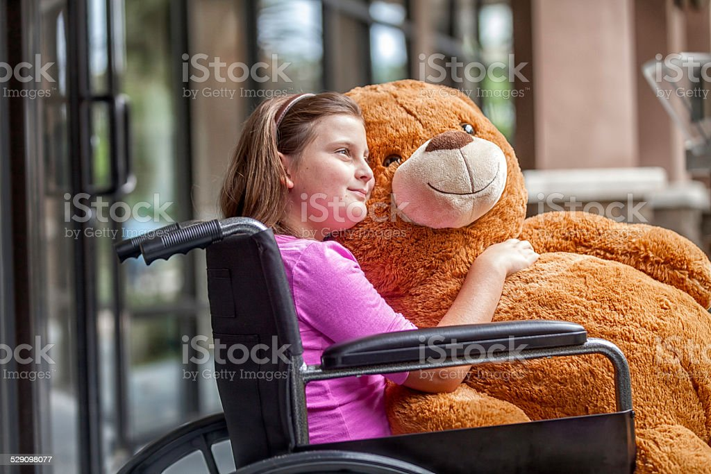 Girl in Wheelchair with a Teddy Bear stock photo