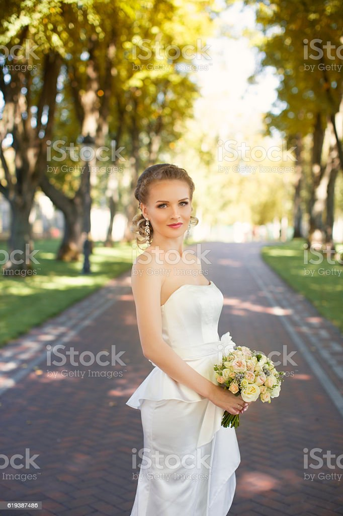 Girl in white dress in the alley in the park stock photo