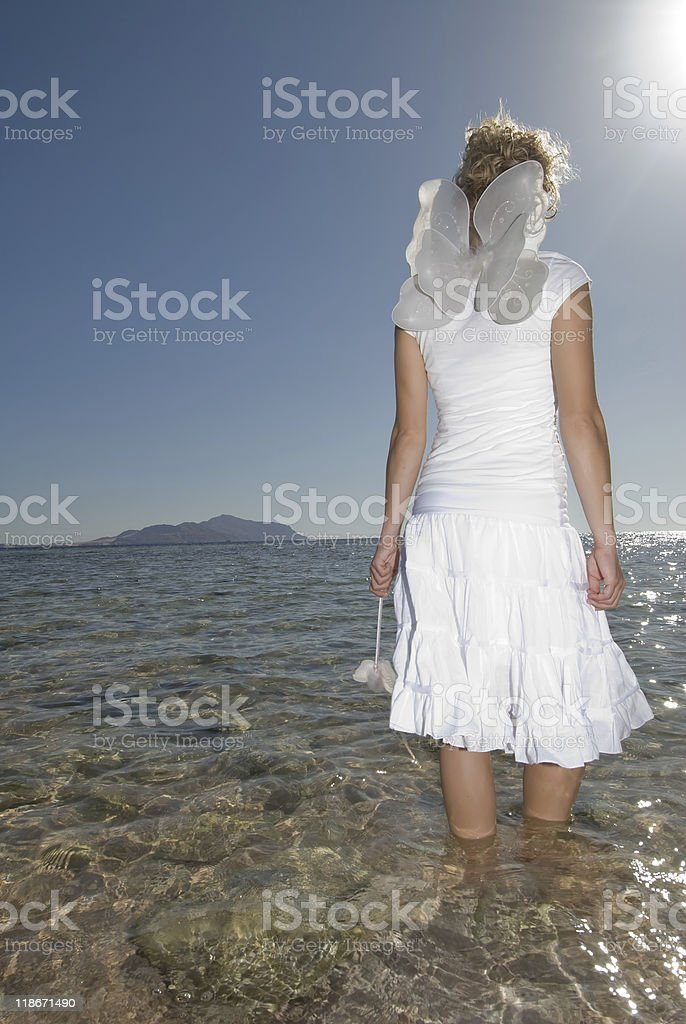 Girl in white dress on sandy beach dressed as a fairy stock photo