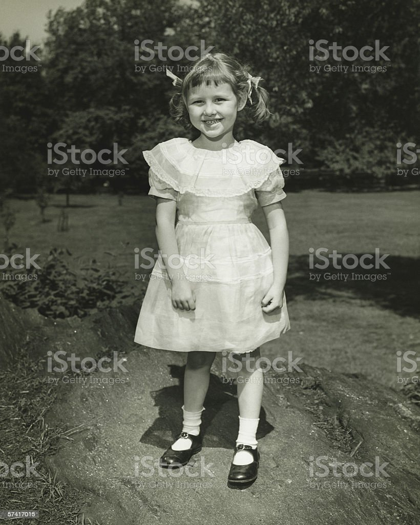 Girl (6-7) in white dress posing in park, (B&W), (Portrait) stock photo