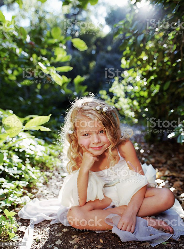 Girl (4-6) in white dress sitting on ground, portrait stock photo