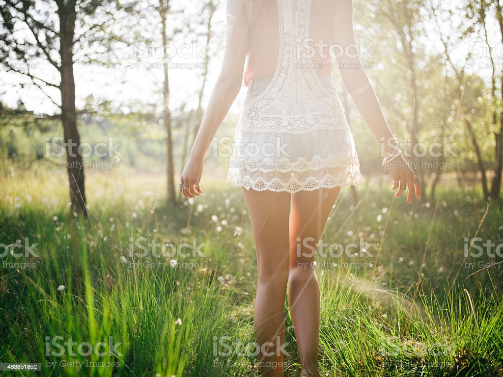 Girl in white dress walking in sunlit summer park stock photo