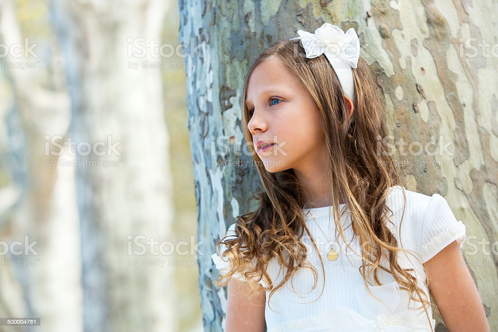 Girl in white standing next to tree. stock photo