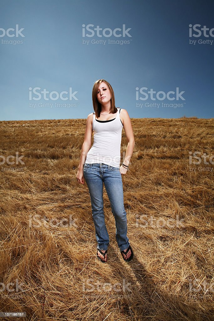 Girl in White Tank Top Posing at a Field royalty-free stock photo