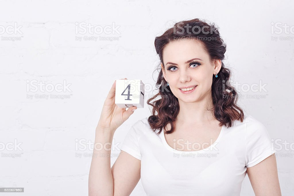 Girl in white t-shirt holding number four. stock photo