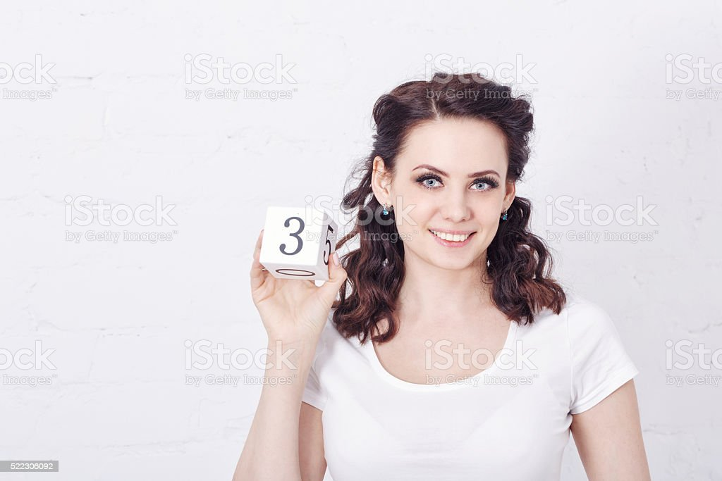 Girl in white t-shirt holding number three. stock photo