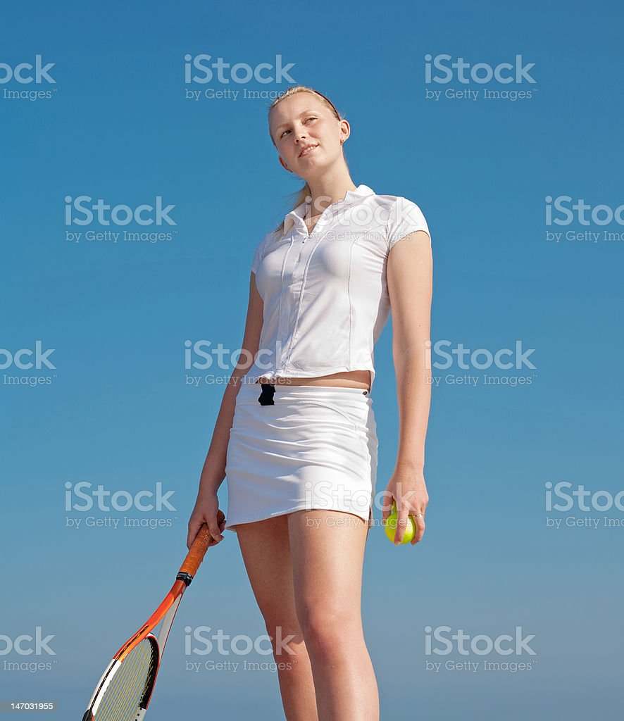 Girl in white with tennis racket on background of sky royalty-free stock photo