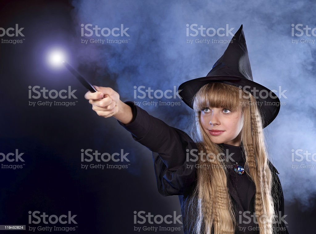 Girl in witch's hat with magic wand. stock photo