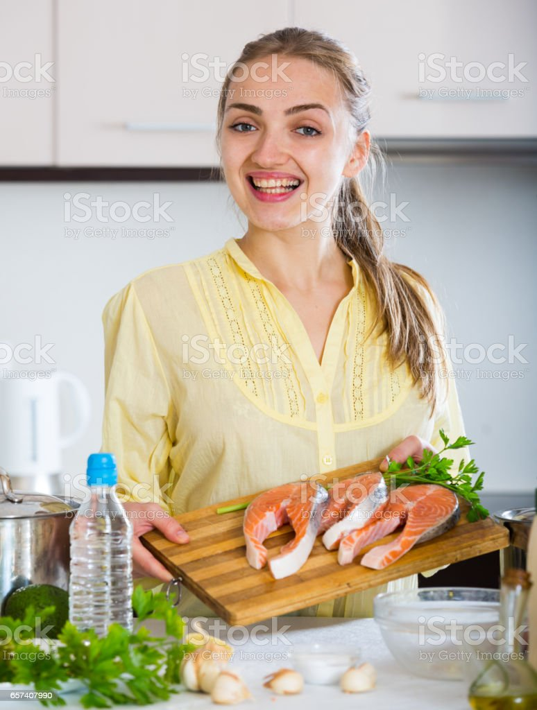 Girl in yellow blouse with fresh salmon fillet stock photo