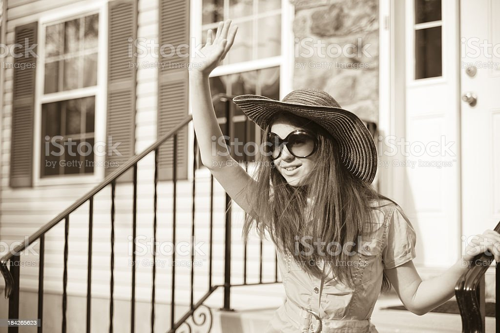 Girl in yellow dress and big hat next to house stock photo