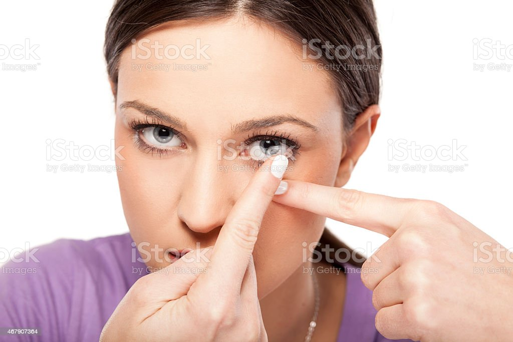 girl inserting contact lens stock photo