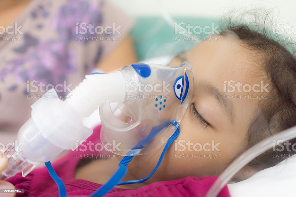 Girl is being applied aerosols inhalation stock photo