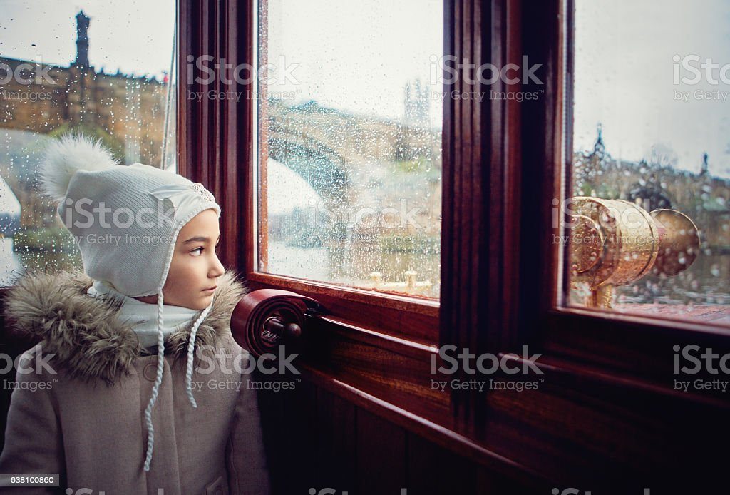 Girl is crossing river in the boat in the rain stock photo