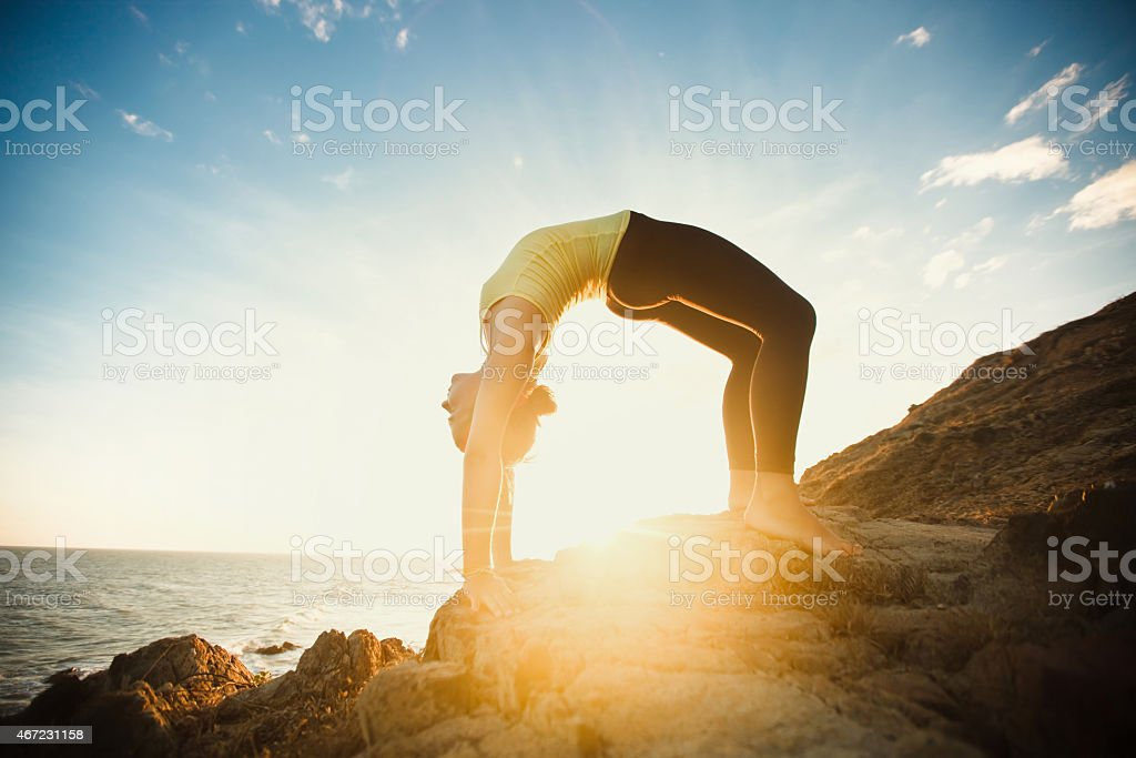 girl is doing yoga  bridge pose by the ocean stock photo