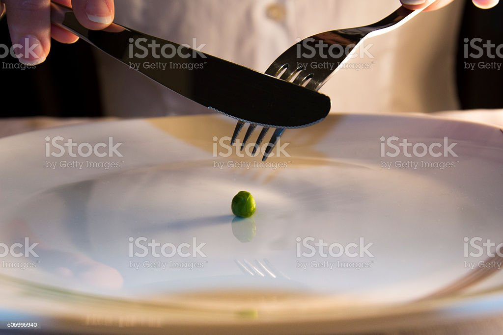 Girl is eating one green pea stock photo