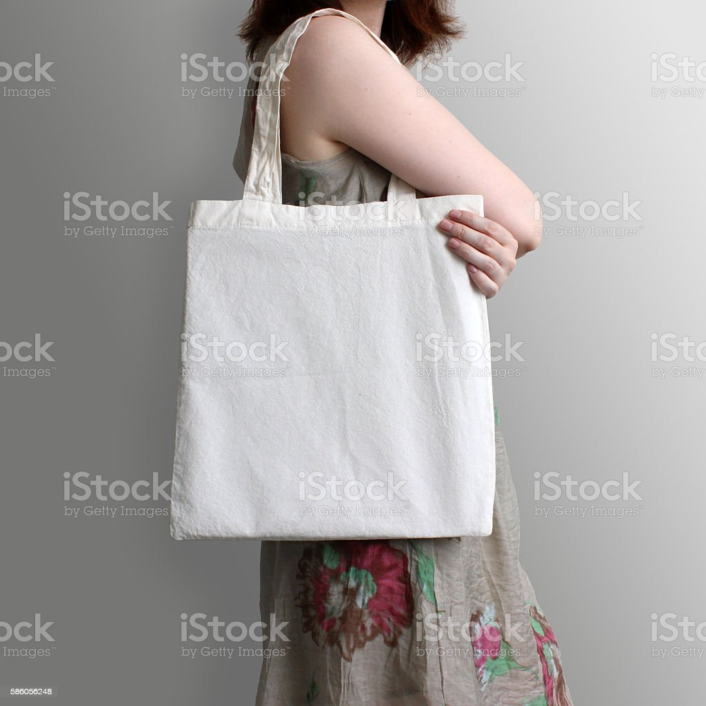 Girl is holding blank cotton eco tote bag, design mockup. stock photo