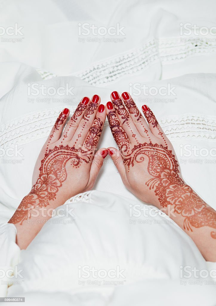 Girl is holding hands with henna tattoos on white dress stock photo