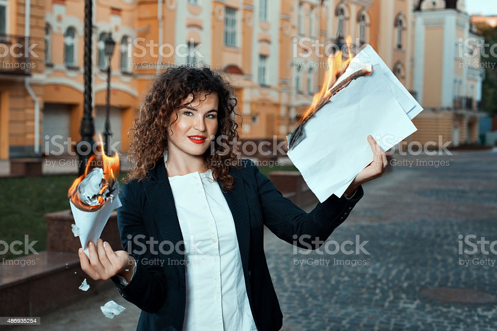 Girl is holding the documents that burn. stock photo