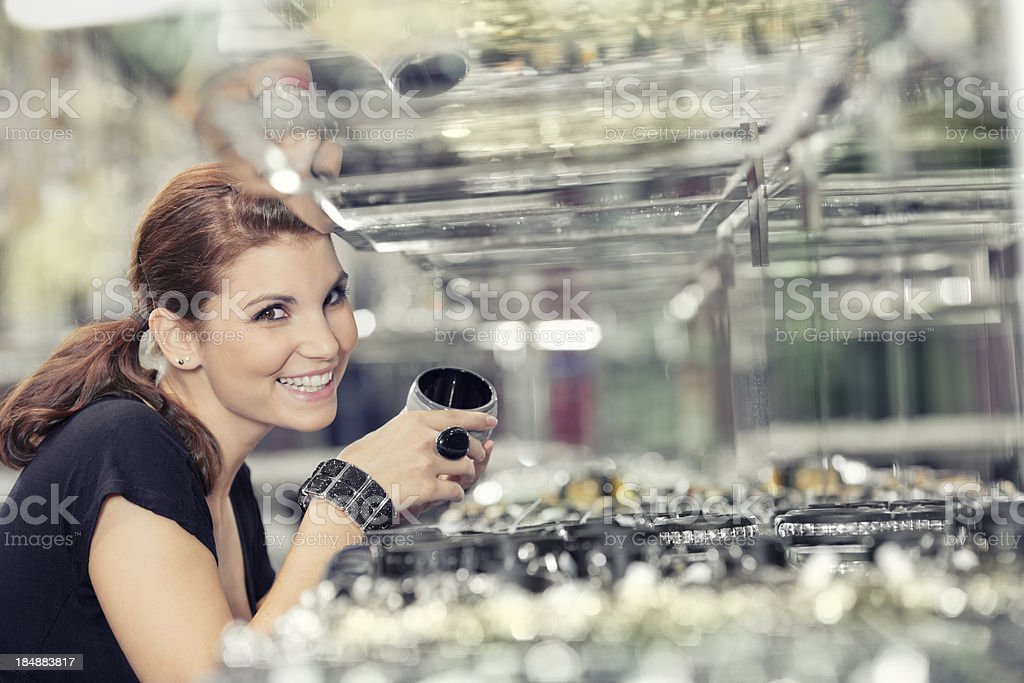 girl is looking at jewelry in jewellers shop stock photo