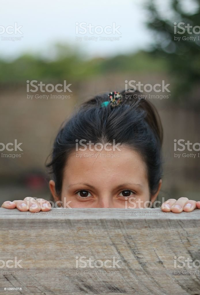 Girl is looking over fence - Stock Image stock photo