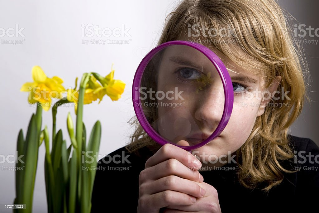 Girl is looking through a magnifying glass royalty-free stock photo