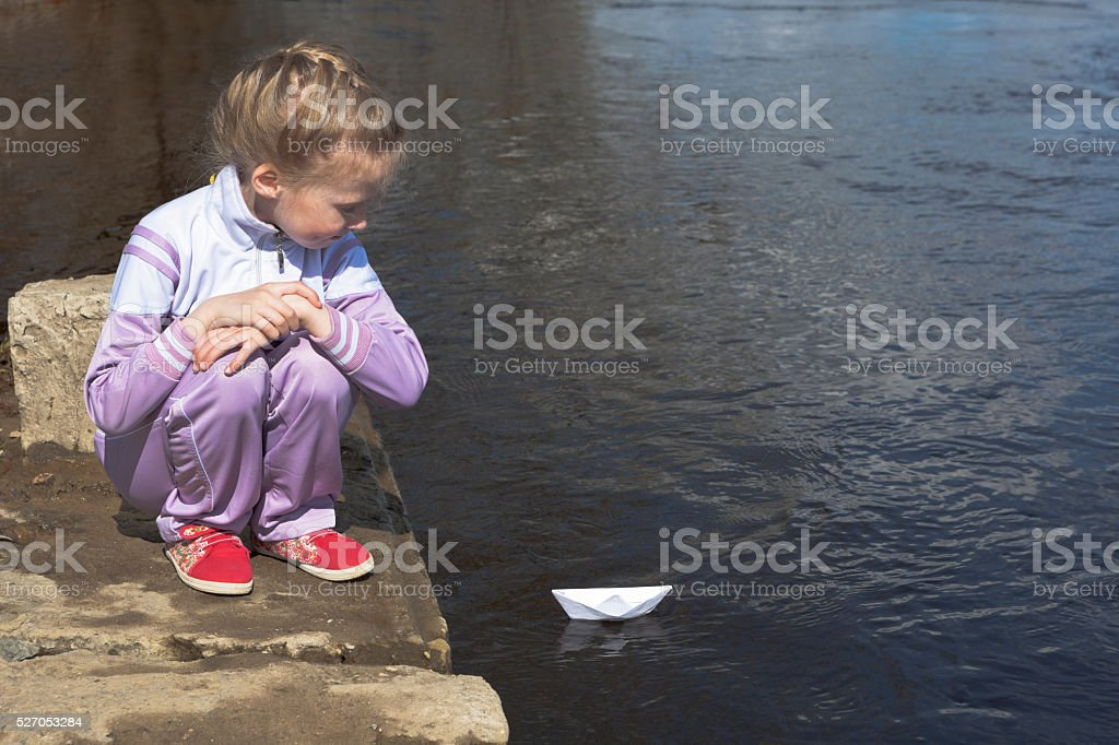 Girl is looks like a paper boat floats away stock photo