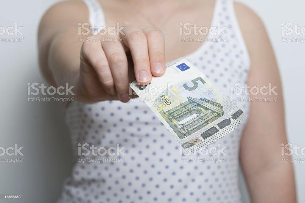 girl is paying with a brand new five euro banknote stock photo