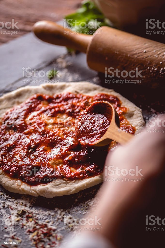 Girl is placing tomato sauce on fresh pizza stock photo