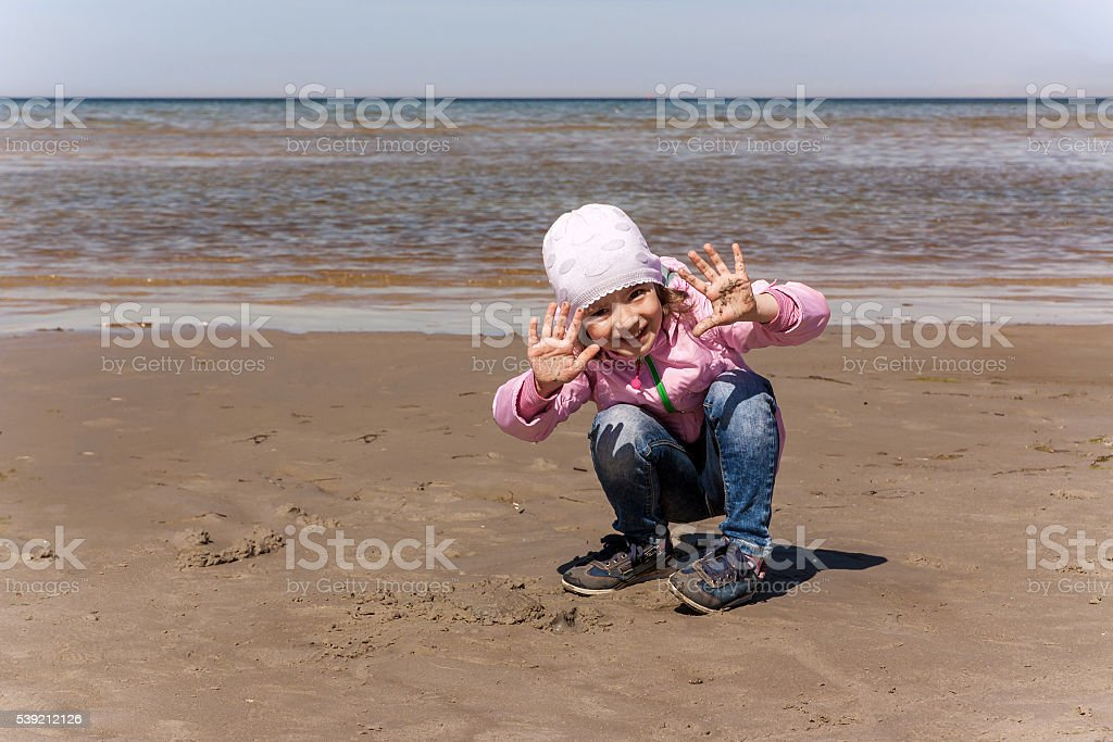 Girl is playing on the sea shore stock photo