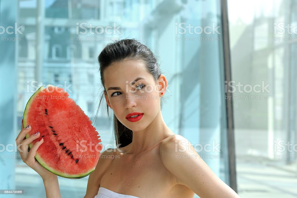 Girl is posing with a slice of red watermelon stock photo