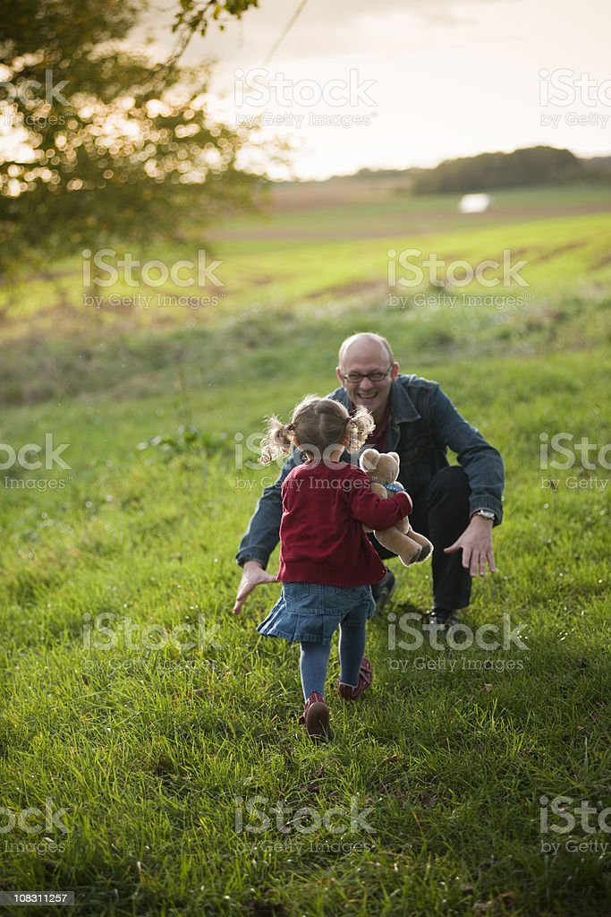 Girl is running in the arms of her grandpa royalty-free stock photo